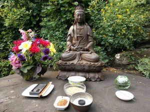 Kuan Yin garden altar, with candles, flowers, water, incense, and a Japanese ink brush.