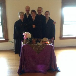 Five smiling Zen practitioners are arranged behind an altar with various Buddha images.