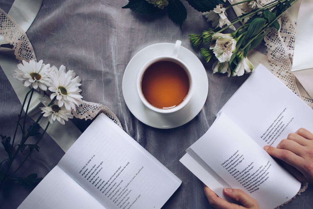 Book reader with tea cup and flowers.