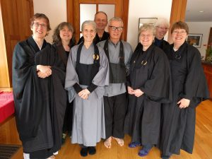 Eight smiling Zen practitioners after a day of deep practice.