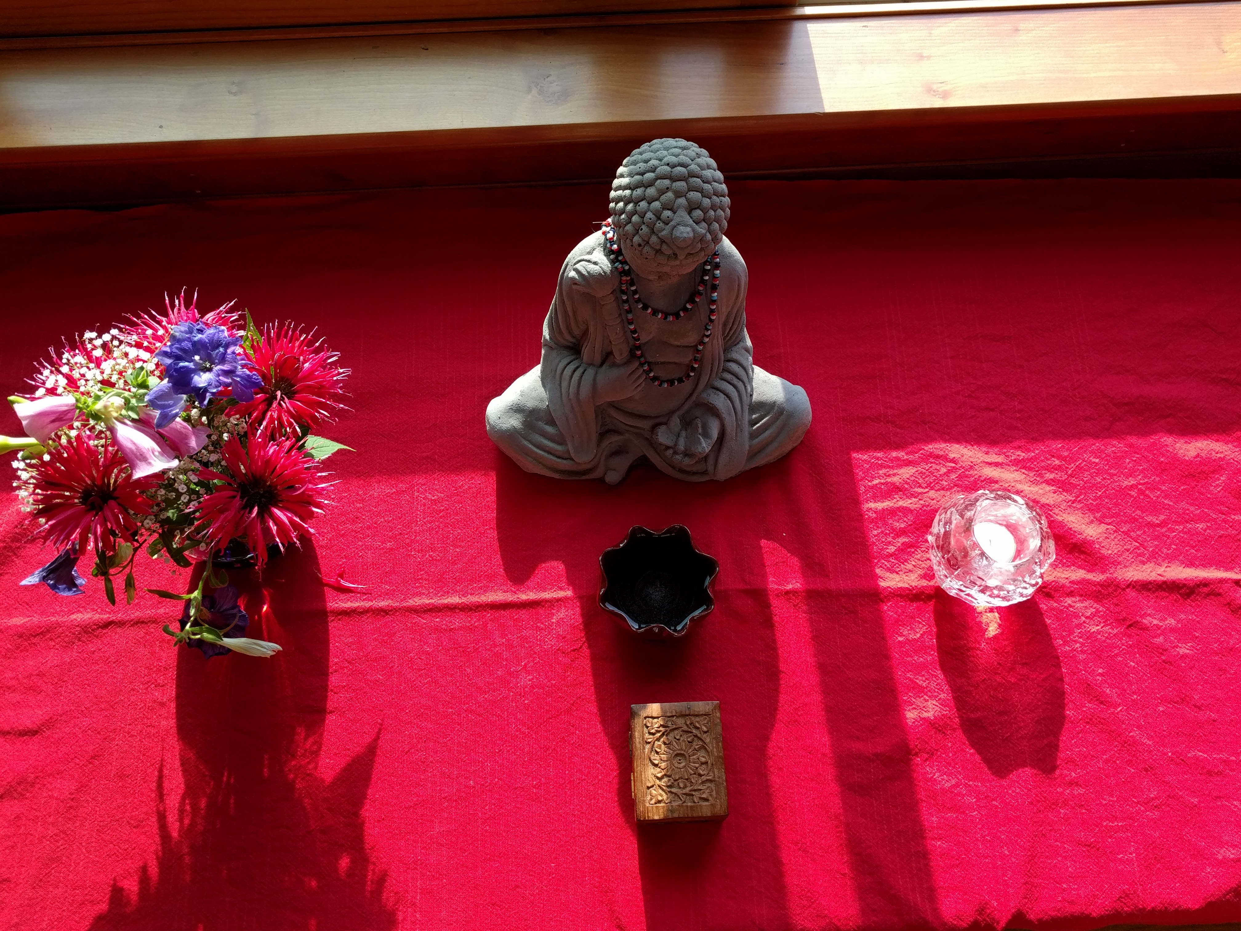 A small stone Buddha flanked by a small summer bouquet of flowers and a tealight candle inside a rough glass container.